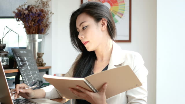 4K-footage-busy-business-woman-working-with-laptop-computer-and-note-book-in-coffee-shop-cafe-in-the-city-in-the-morning-business-people-lifestyle-Asian-model-in-her-30s