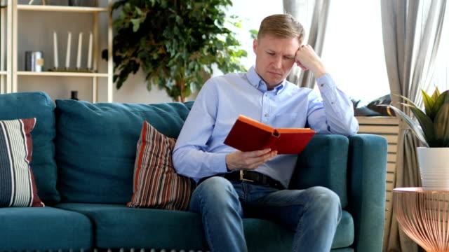 Medio-de-años-hombre-durmiendo-mientras-que-libro-de-lectura-sentado-en-el-sofá
