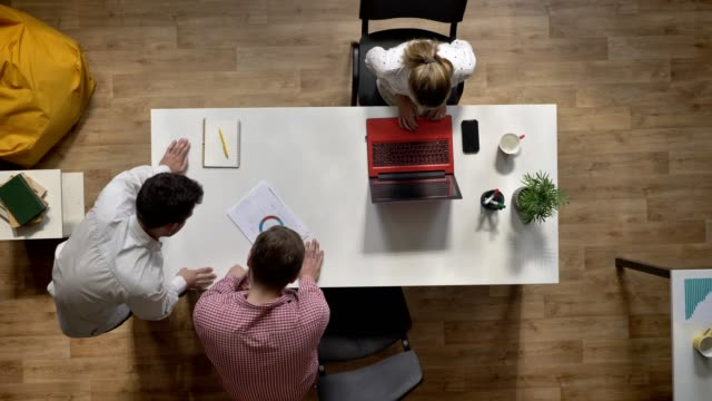 Zwei-Männer-diskutieren-Projekt-wenn-Frau-am-Laptop-arbeiten-und-sitzen-am-Tisch-im-modernen-Büro-Topshot