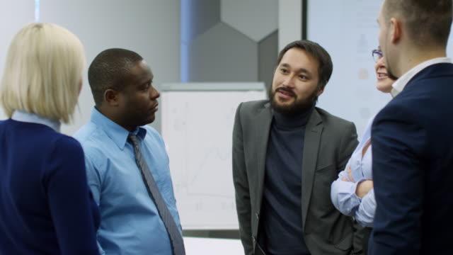 Empresario-asiático-sonriente-hablando-con-colegas