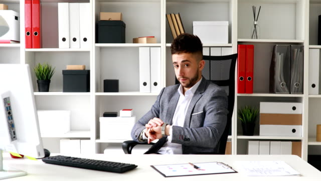 young-businessman-in-gray-jacket-sitting-at-table-in-white-office-looking-at-clock-and-leaving-on-chair