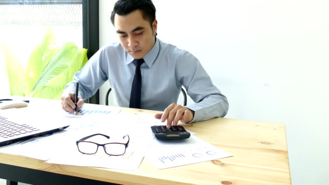 Businessman-analyzing-investment-charts-with-calculator-laptop-Accounting-and-technology-in-office-Business-people-using-laptop-at-office-Analyze-plans-