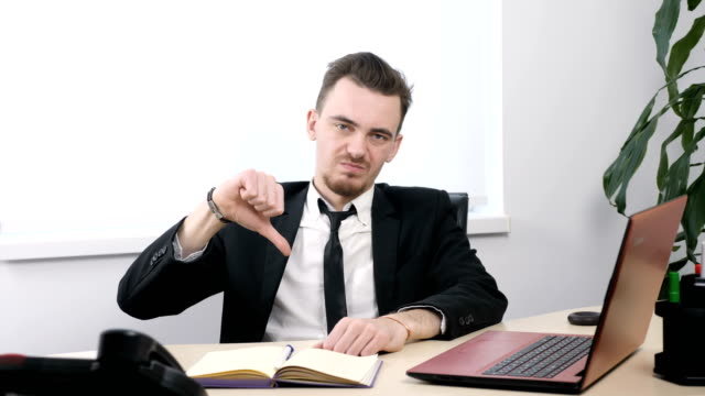 Young-businessman-in-suit-sitting-in-office-and-showing-thumbs-up-sign-60-fps