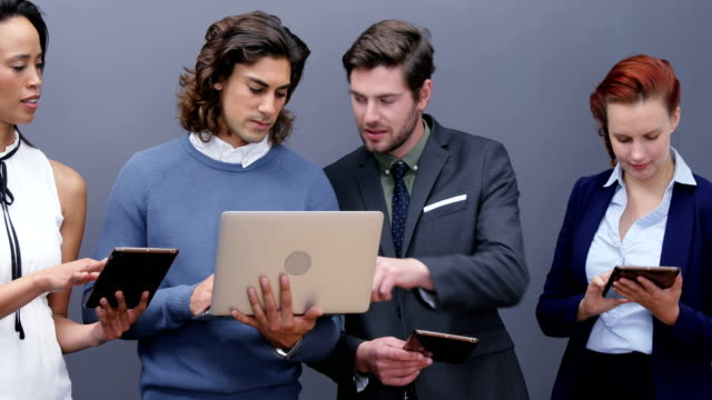 Group-of-executives-using-laptop-and-digital-tablet-4k