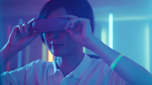 East-Asian-Pro-Gamer-Wearing-Virtual-Reality-Headset-Plays-Online-Video-Game-with-Joysticks-/-Controllers-Cool-Retro-Neon-Colors-in-the-Room-