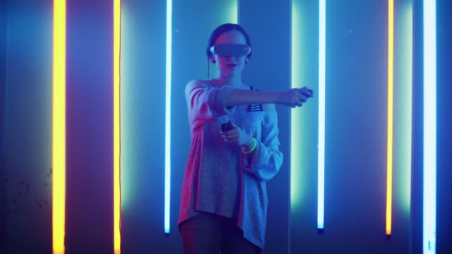 Beautiful-Young-Girl-Wearing-Virtual-Reality-Headset-Draws-Abstract-Lines-and-Figures-with-Joysticks-/-Controllers-Creative-Young-Girl-Does-Concept-Art-with-Augmented-Reality-Playing-Online-Video-Game-Neon-Retro-Lights-Surround-Her-
