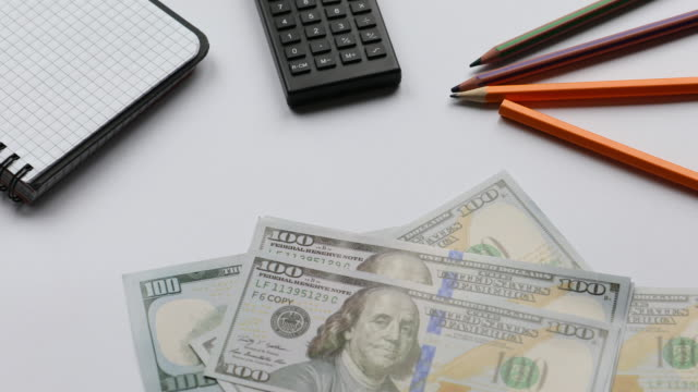 Contar-dinero-en-la-mesa-de-trabajo-paquete-de-dólares
