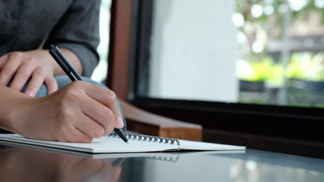 A-woman-s-hand-writing-down-on-a-white-blank-notebook-on-table