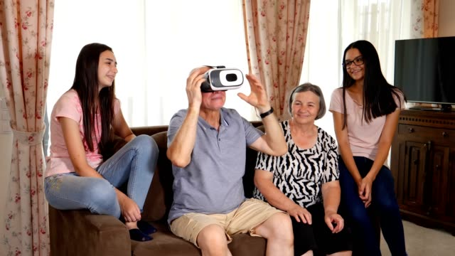 Senior-man-in-virtual-reality-headset-or-3d-glasses-having-fun-with-family