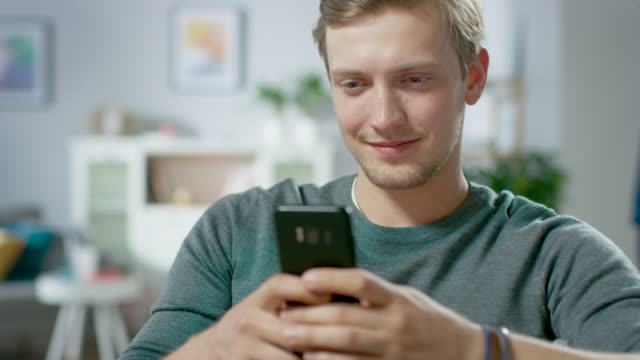 Portrait-of-the-Handsome-Young-Man-Using-Smartphone-Browsing-in-Internet-Checking-Social-Networks-while-Sitting-At-Home-