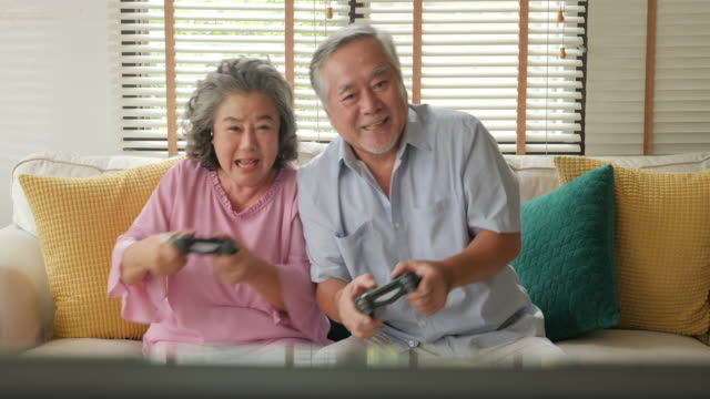 Asian-senior-couple-playing-game-together-at-home-with-happy-emotion-People-with-relaxation-old-age-retirement-senior-lifestyle-family-concept-