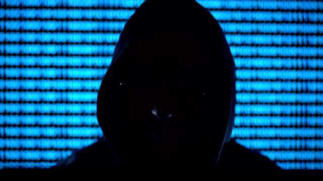Hacker-trabajando-en-una-computadora-fondo-azul-datos-digitales-de-desplazamiento