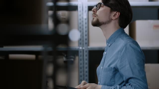 Jefe-de-inventario-de-almacén-aplicaciones-Smartphone-dispositivo-para-verificar-existencias-en-los-estantes-Filas-de-estantes-con-paquetes-de-caja-de-cartón-llena-de-productos-listos-para-su-envío-