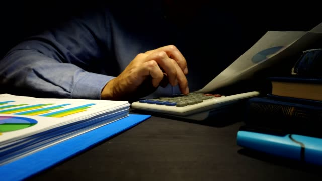 Hombre-de-negocios-utiliza-la-calculadora-para-comprobar-el-informe-financiero-