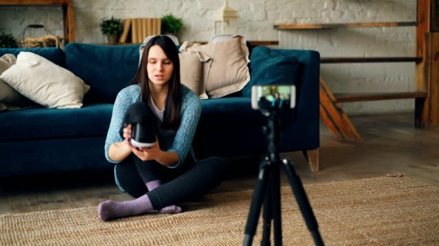 Attractive-lady-vlogger-is-using-smartphone-camera-to-record-video-about-virtual-reality-glasses-Girl-is-holding-device-showing-it-to-subscribers-and-talking-