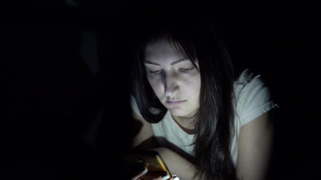 Mujer-joven-en-la-oscuridad-por-la-noche-se-sienta-con-un-teléfono-en-las-redes-sociales