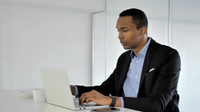 Lässige-afroamerikanischer-Geschäftsmann-trinken-Kaffee-während-der-Arbeit-am-Laptop