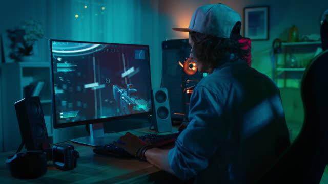 Profi-Gamer-spielen-Ego-Shooter-Online-Video-Spiel-auf-seiner-leistungsstarken-PC-mit-bunten-Neon-Led-Leuchten-Junge-Mann-trägt-eine-Kappe-Wohnzimmer-mit-warmen-Lampen-beleuchtet-\-Nabend-
