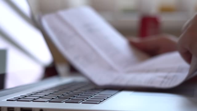 Closeup-of-hands-working-and-typing-on-a-laptop-keyboard-with-black-keys-in-the-process-of-work-a-man-looks-at-paper-documents