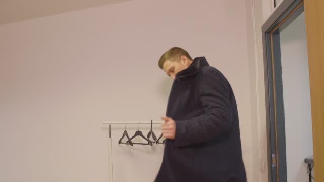 Junger-Geschäftsmann-Eingabe-im-Büro-Mantel-ausziehen-und-Kleiderbügel-hängen
