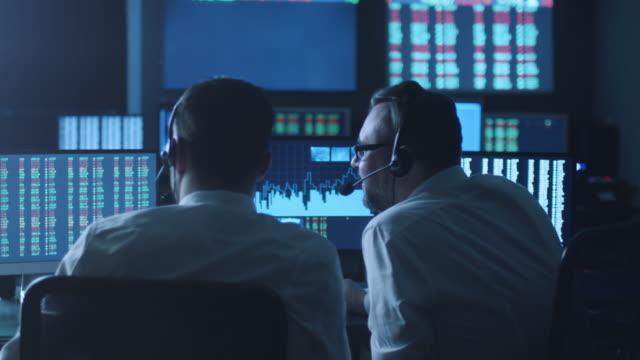 Equipo-de-agentes-de-bolsa-se-están-tener-una-discusión-en-la-oficina-de-oscuridad-con-pantallas-