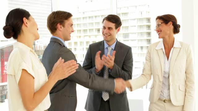 Geschäftsleute-schütteln-die-Hände-beim-Gespräch-während-andere-begrüßen