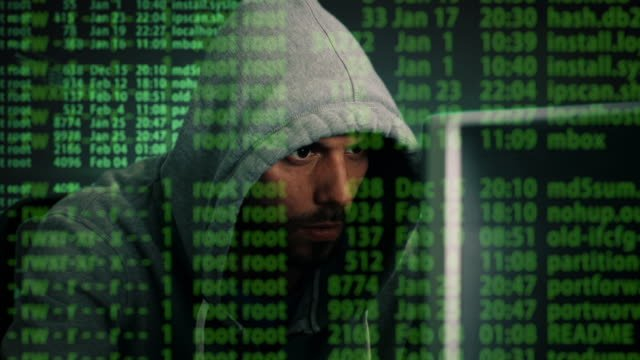 Close-up-Mid-Shot-of-a-Hacker-Wearing-Hoodie-Sitting-at-His-Desktop-Computer-Special-Effects-of-Hacking-Process-Shown-all-over-the-Screen-
