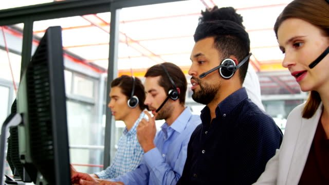 Business-executives-with-headsets-using-computer