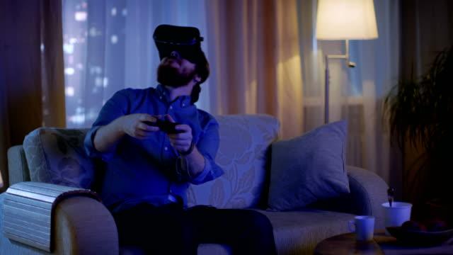 Hombre-sentado-en-un-sofá-en-el-salón-de-juegos-Video-juegos-en-su-consola-mientras-lleva-puesto-el-casco-de-realidad-Virtual-
