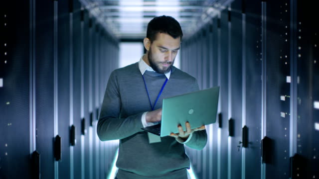 Male-IT-Engineer-Works-on-a-Laptop-in-a-Big-Data-Center-Rows-of-Rack-Servers-are-Seen-