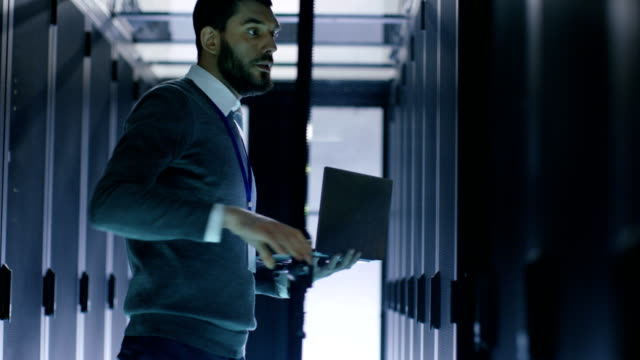 Male-IT-Engineer-Opens-Server-Cabinet-while-Holding-Laptop-He-Works-in-Big-Data-Center