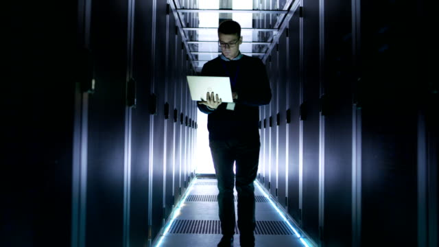 Male-Server-Engineer-Walks-with-Open-Laptop-Through-the-Rows-of-Rack-Servers-He-s-Working-in-Big-Futuristic-Data-Center-