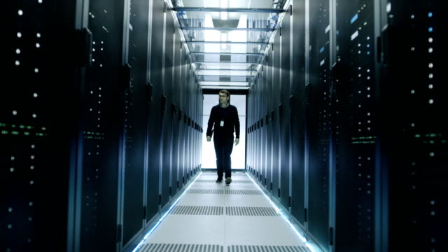Frontal-View-of-IT-Engineer-Walking-Through-Data-Center-with-Working-Rack-Servers-