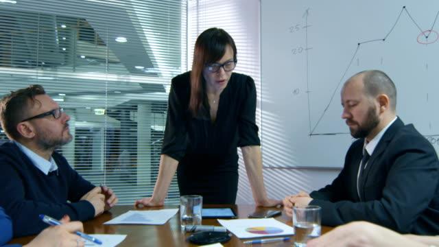 Empresaria-está-haciendo-una-presentación-para-un-equipo-de-empleados-que-están-sentados-en-una-sala-de-reuniones-