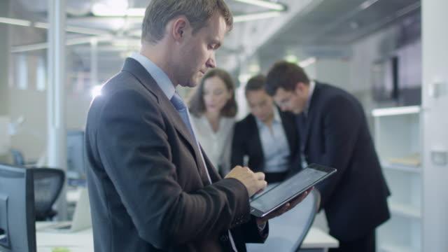Empresario-trabajando-en-la-tableta-en-la-oficina-abarrotada
