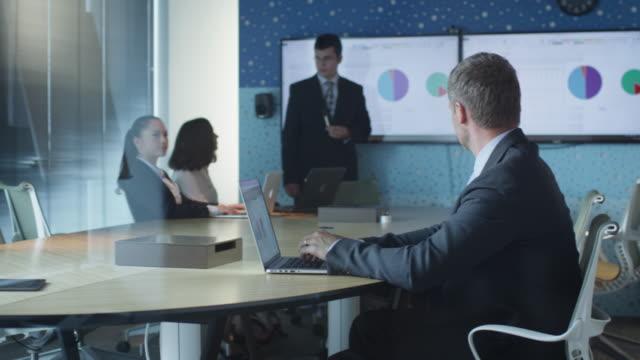 Geschäftsmann-arbeitet-an-Laptop-während-der-Präsentation-im-Konferenzraum