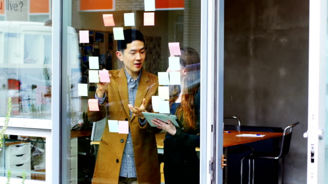 Business-executives-discussing-over-sticky-notes