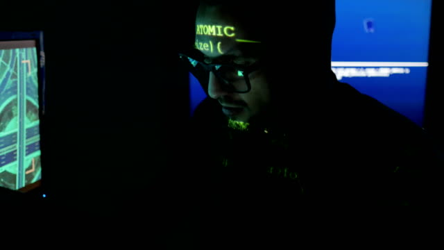 Male-hacker-working-on-computer-while-green-code-characters-reflect-on-his-face-in-a-dark-office-room-IT-professional-programmer-in-glasses-is-working
