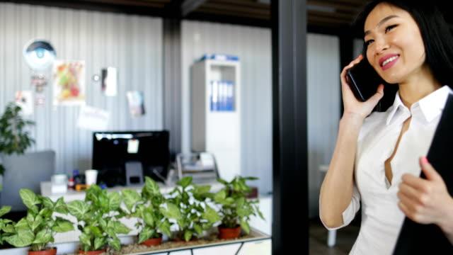 Mujer-de-negocios-asiática-hablando-en-llamada-telefónica-con-documentos-en-oficina-creativa-moderna-hermosa-empresaria-trabajo