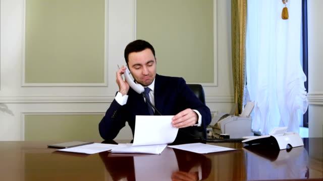 Joven-empresario-de-éxito-seguro-trabajando-en-oficina-moderna-analizando-negocios-por-conversación-telefónica