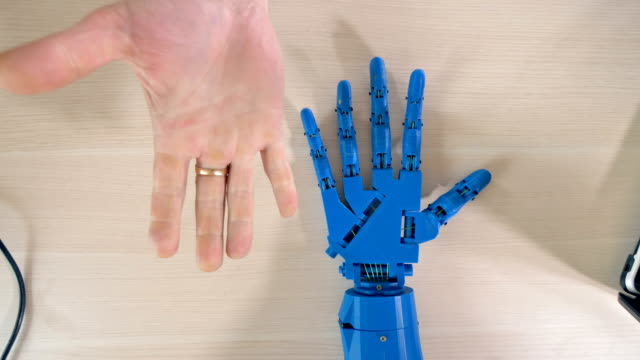 Mano-robótica-repitiendo-movimientos-de-mano-derecha-del-hombre-