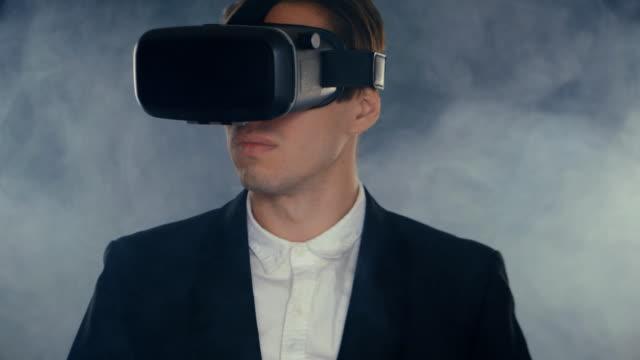 Businessman-get-experience-in-using-VR-headset-in-smoky-dark-room