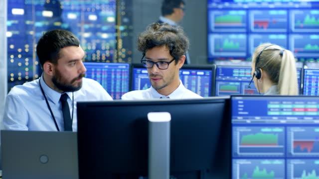 Broker-profesional-consulta-Trader-de-bolsa-en-su-sitio-de-trabajo-Equipo-multiétnico-en-la-oficina-de-bolsa-de-valores-es-ocupado-venta-y-compra-de-acciones-en-el-mercado-Las-pantallas-muestran-números-de-datos-relevantes-