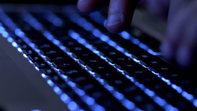 Typing-on-the-illuminated-laptop-at-night