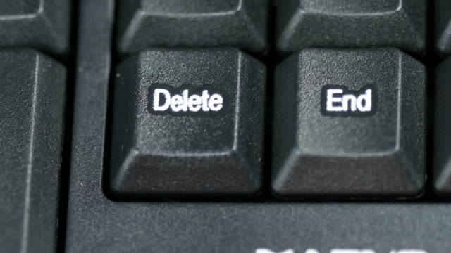 Close-up-of-human-finger-pushing-an-delete-button-on-the-computer-keyboard