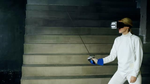 Konzentrierte-Fechter-Frau-Praxis-Fechten-Übungen-mit-VR-Kopfhörer-und-training-Simulator-Wettbewerb-Spiel-drinnen