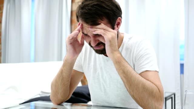 Depressionen-Kopfschmerzen-betonte-Bart-Mann-zu-Hause