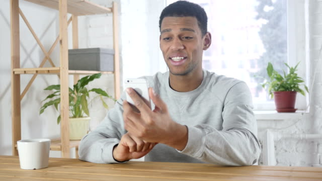 Chat-de-smartphone-Video-por-joven-Afro-Americana-en-oficina