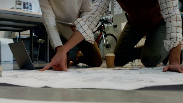 Kolleginnen-und-Kollegen-diskutieren-über-Blueprint-miteinander-4k