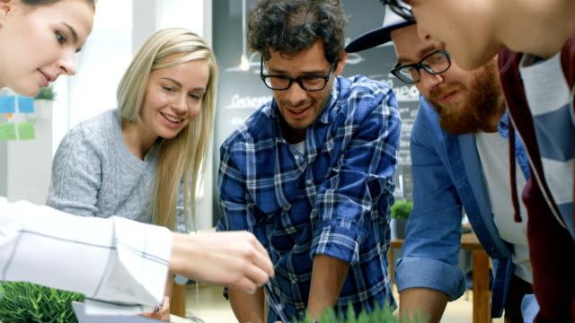 Team-von-jungen-kreativen-Entwickler-haben-Brainstorming-Sitzung-Besprechungstisch-diskutieren-Ideen-und-neue-Konzepte-Stilvolle-Menschen-in-trendigen-Büroumgebung-